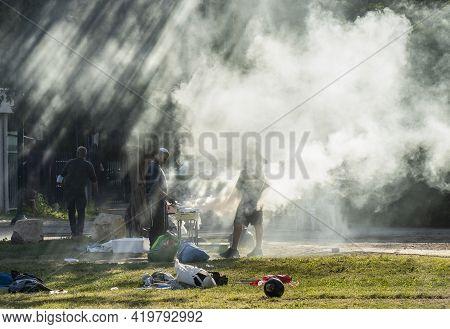 Tel Aviv, Israel - March 31st, 2021: Two Men Preparing A Barbecue In A Tel Aviv Park On A Sunny Morn