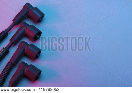 Black Ignition Wires Of A High Voltage For Spark Plug On Blue And Red Background. Car Parts. Top Vie