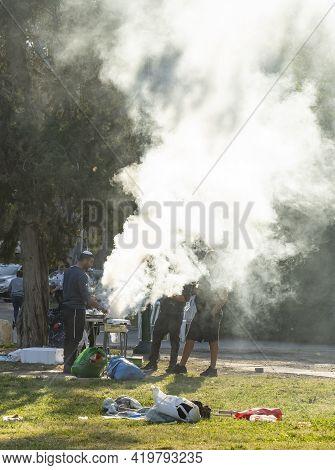 Tel Aviv, Israel - March 31st, 2021: Three Men Preparing A Barbecue In A Tel Aviv Park On A Sunny Mo