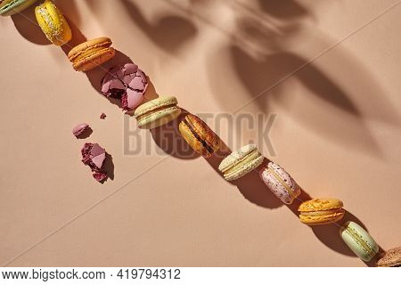 Diagonal Line Of Whole Macarons With One Bitten Cookie On Beige Background
