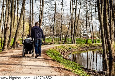 View From Back To A Woman In Wheelchair And A Man Walking And Having Conversation In A Park Near Riv