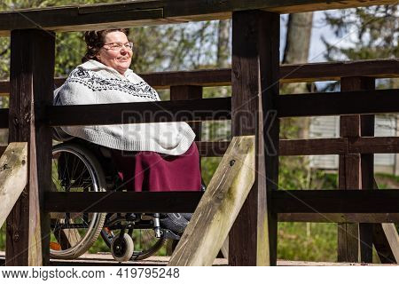 Interesting Angle For Woman In Wheelchair On Bridge. Happy Mid-age Women With Wheelchair Enjoying Sp