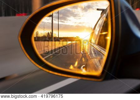 Rear View Car Mirror View Back To Nature On Evening With Sunset. Sunset Reflected In The Mirror Of T