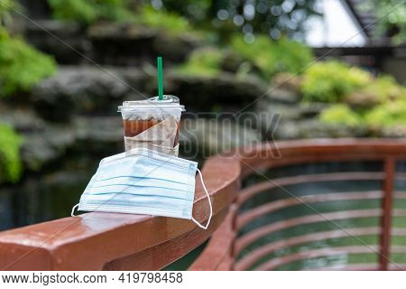Iced Coffee Mugs Are Placed In Public Places With A Medical Mask On Them.