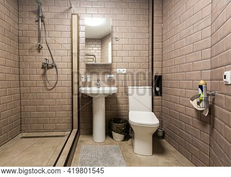 Bathroom Covered Brown Tiled, Mirror And Sanitary Engineering Is In The Apartment That Is Afer Const