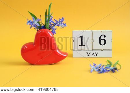 Calendar For May 16 : A Bouquet In A Heart-shaped Vase With Blue Flowers And The Numbers 16 On Cubes