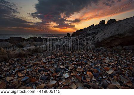 Russia. Dagestan. Dawn On The Seashell-strewn Rocky Shore Of The Caspian Sea Near The City Embankmen