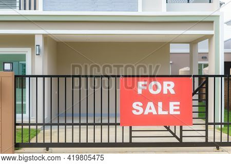 House Sale Sign Hanging On The Fence Of The House Door To Announce To Interested Parties To Contact.