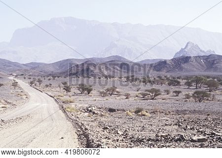 Dirt Road Through Desert In Oman Near Al Ayn With Mountains In Background