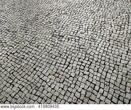 Portuguese Cobblestone Pavement. Detail Of Typical Handmade Sidewalk, Pedestrian Perspective. Textur