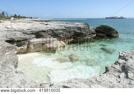 The Little Beach Surrounded By Eroded Steep Rocks On Grand Bahama Island Shore.