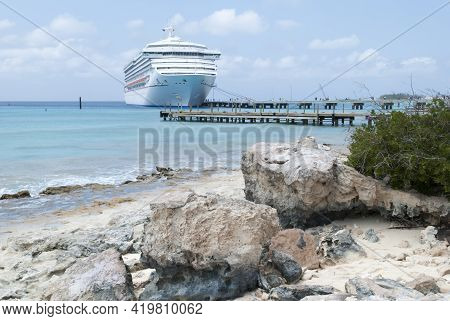 The View Of A Rocky Beach And A Cruise Ship Moored To The Pier On Grand Turk Island (turks And Caico