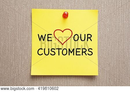 Text We Love Our Customers Handwritten On Yellow Sticky Note. Customer Satisfaction Concept.