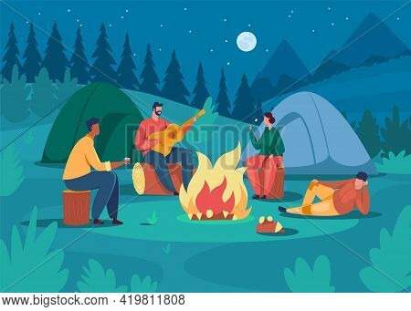 People Camping At Night. Friends Sitting Near Campfire, Playing Guitar, Roasting Marshmallow. Touris