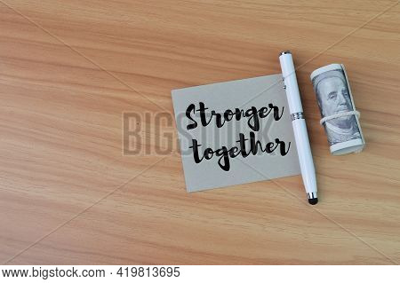 Top View Of Pen, Money Banknote And Memo Note Written With Stronger Together
