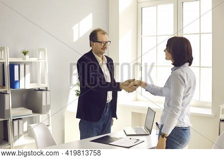 Bank Worker, Loan Adviser Or Insurance Agent Shaking Hands With Client In His Office