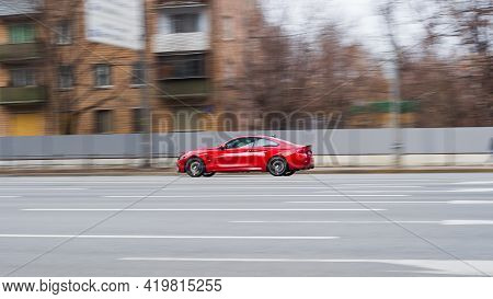 Red Aggressive Bmw Sport Car Riding On The Road. Side View Of Shiny Bmw M4 F82 Driving In The Street