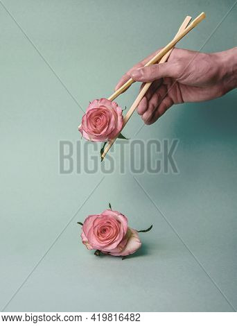 Pink Rose Flowers In Young Hands With Sticks In Pastel Colors. A Minimal Concept Of Nature. Advertis