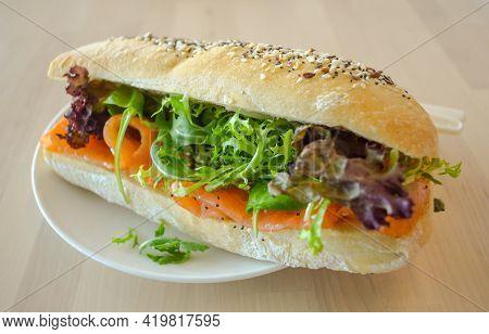 Baguette Sub Sandwich With Smoke Salmon Fish, Rocket Lettuce, Red Oak Lettuce On The Table.