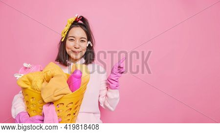 Pleased Asian Woman Housekeeper With Dark Hair Wears Sweatshirt And Protective Rubber Gloves Holds L