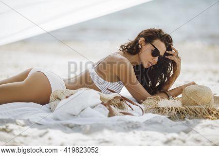 Woman In Bikini Tanning On The Beach During Summer Sea Vacation.