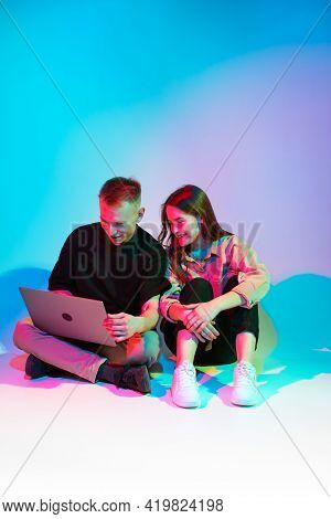 Happy Young Creative Team Girl And Guy Working On Laptop Or Making Home Work. Technologies And Educa