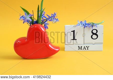 Calendar For May 18 : Bouquet In A Heart-shaped Vase With Blue Flowers And The Numbers 18 On Cubes,