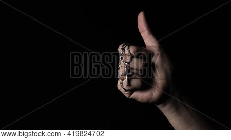 Praying With A Rosary. Hand Of Catholic Man With Rosary On Black Background.