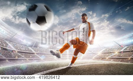 Professional Soccer Player In Action On Stadium With Flashlights And Fans. Kicking Ball For Winning