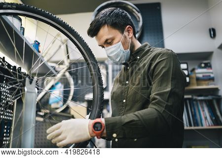 Bicycle Mechanic Wearing Protective Mask And Gloves Repairs Customers Bicycle Wheel In Accordance Wi