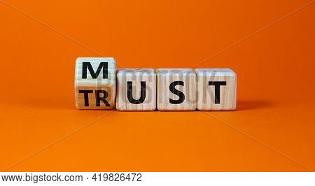 Must Trust Symbol. Turned Wooden Cubes With Words 'must Trust'. Beautiful Orange Table, Orange Backg