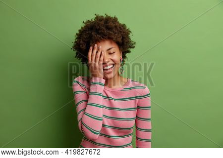 Studio Shot Of Happy African American Woman Makes Face Palm Smiles Broadly Has Fun Laughs Out Loudly