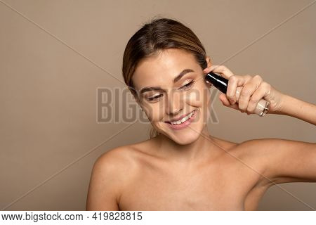 A Beautiful Smiling Model Applies Foundation From A Glass Tube. Applying Makeup To The Face, Smoothi