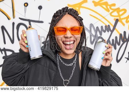 Overjoyed Dark Skinned Woman Has Dreadlocks Feels Very Happy Draws Graffiti With Aerosol Spays Has F