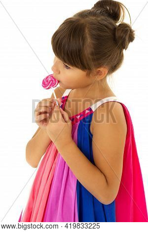 A Beautiful Girl Licks A Lollipop. Cute Girl In A Bright Summer Dress Posing In The Studio On An Iso