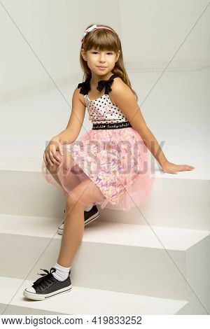 Stylish Girl Sitting On White Staircase. Girl Wearing Nice Dress And Sneakers Sitting On Step Leanin