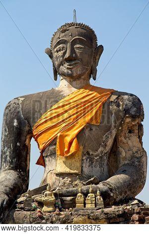 Closeup Of Huge Stone Statute Of Buddha Wrapped In Orange Clock Monastry Phonsavan, Laos.