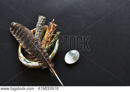 A Top View Image Of Healing Smudge Sticks And Sacred Feather On A Black Background.