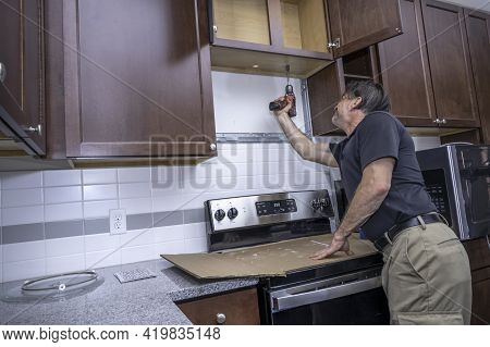 An Appliance Technician Or Diy Repairman Drilling A Hole Through A Cabinet For A Microwave Installat