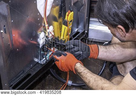 Close Up Of Hands From An Appliance Technician Testing A Component On An Electric Range For Voltage