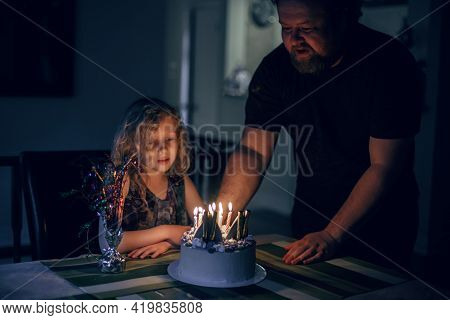 Cute Funny Blonde Girl Blowing Candles On Birthday Cake In Dark Room. Happy Birthday Party Celebrati