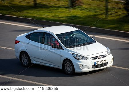 Alanya, Turkey  - April 17  2021:    White Hyundai Solaris   Is Driving Fast On The Street On A Warm