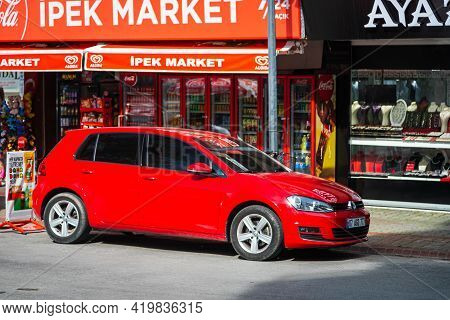 Alanya, Turkey - April 17 2021: Red Volkswagen  Golf  Is Parked  On The Street On A Warm Summer Day