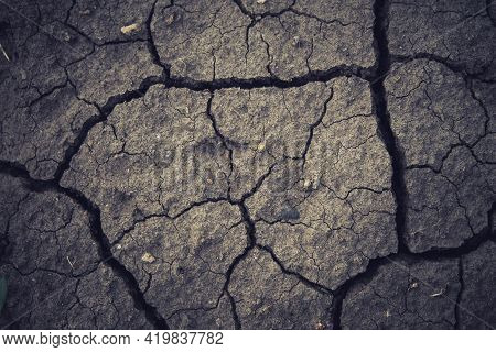 Deep Cracks In The Ground. The Dry Ground Cracked. Black Soil With Deep Splits. The Consequences Of