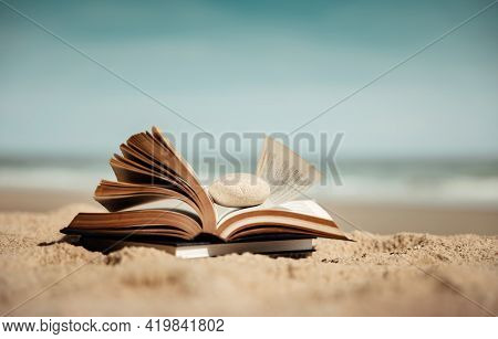 Reading Book Outdoor In Summer Concept. Opened Book On The Beach Sand In Front Of The Sea On Sunny D
