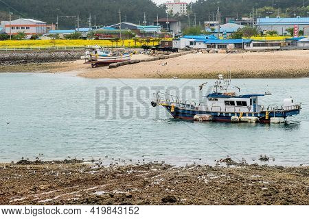 Sinjindo, South Korea; April 30, 2021: Loan Fishing Trawler In Shallow Water With Buildings On Shore