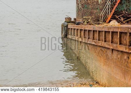 Side View Of Beached Old Rusty Barge With Stern Resting In Shallow Water.