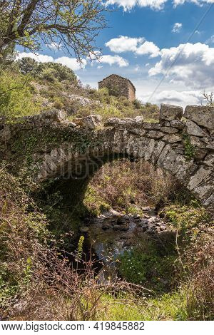 A Small Genoise Bridge Over A Stream In The Balagne Region Of Corsica With An Ancient Stone Farm Bui