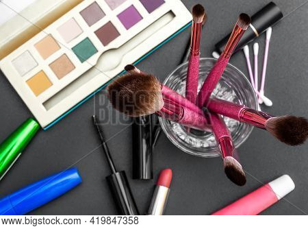 Professional Makeup Brushes With Other Cosmetics Tools On Black Desk. Top View.