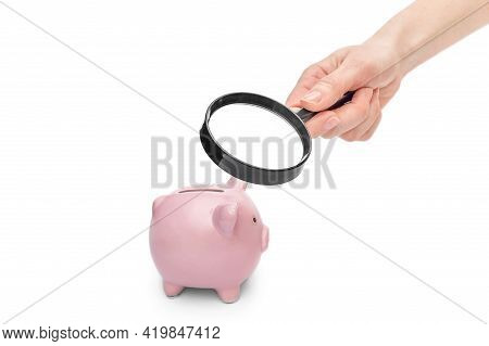 Hand With Magnifying Glass Examining Piggy Bank On White Background. Researching Savings.